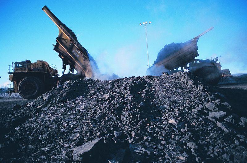 Oil sands mine trucks unloading ore